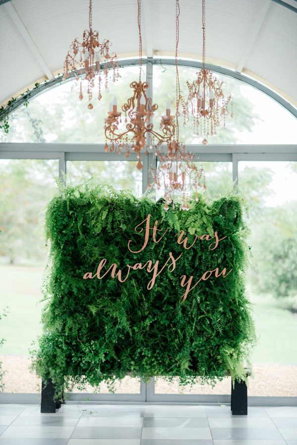Green wall comes to live with pink peonies and copper metalics.