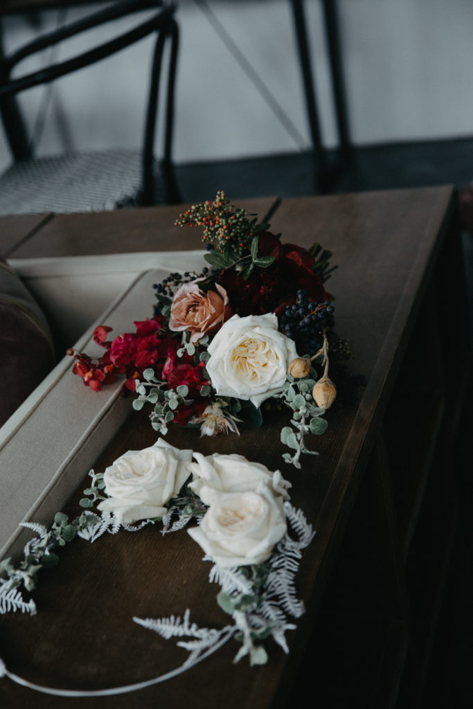 Burgundy winter wedding with hanging flowers, naked bulbs, round arch and berry textures.
